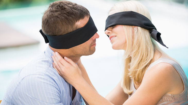 a couple kissing while blindfolded