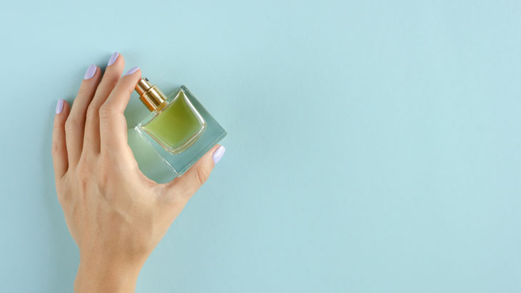 hand holding a small perfume bottle