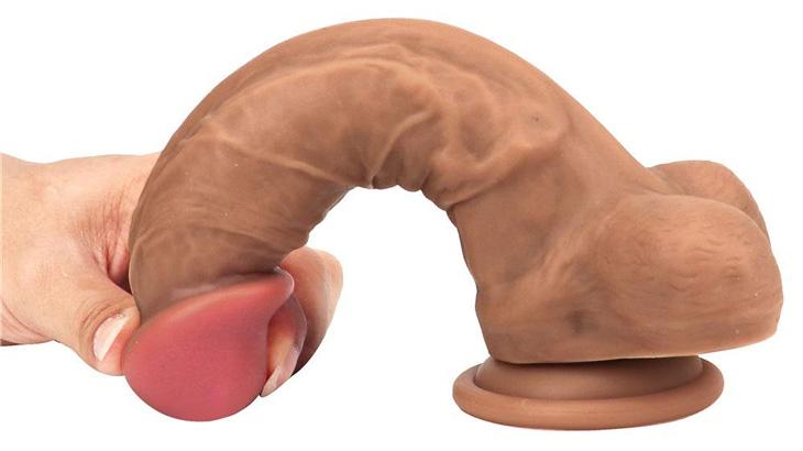 A hand bending a dildo